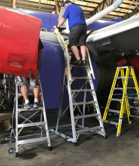 10 Foot Cowl Pylon Max Next To 6 Foot Lnc Pylon With Technicians Servicing Engine Area Of Boeing 737 Max