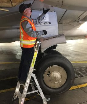5 Foot Mini Pylon With Technician About To Access Panel Above Wheel Of Boeing 737 On Tarmac