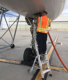 5 Foot Mini Pylon With Technician Feeding In Hose To Boeing 757 On Tarmac Second Shot