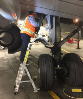 5 Foot Mini Pylon With Technician Working Inside Gear Well Access Panel Above Wheel Of Boeing 737