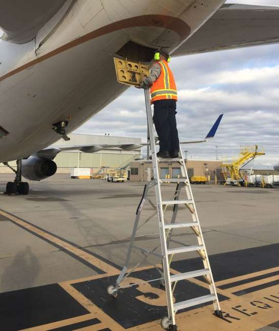 11 Foot Lnc Pylon With Technician In Aftp Apu Access Door On Underside Of Tail On Boeing 757 On Tarmac