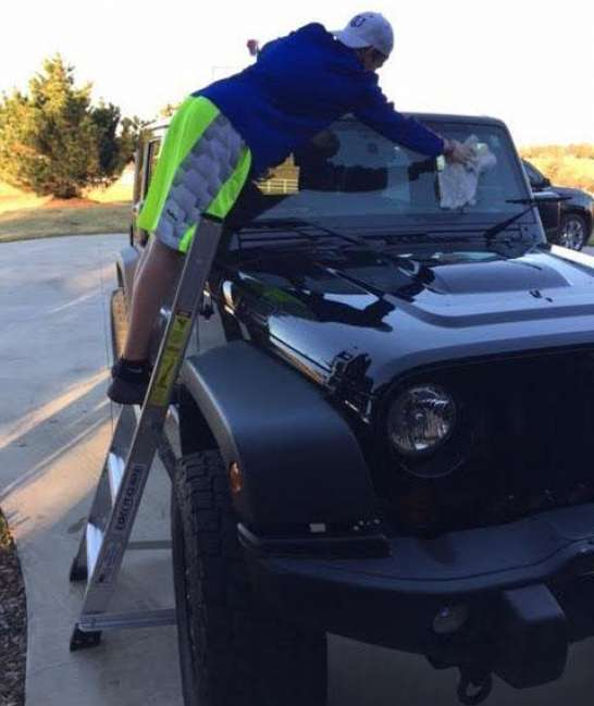 5' LNC Lite Aluminum Ladder front shot of reaching across windshield on Jeep