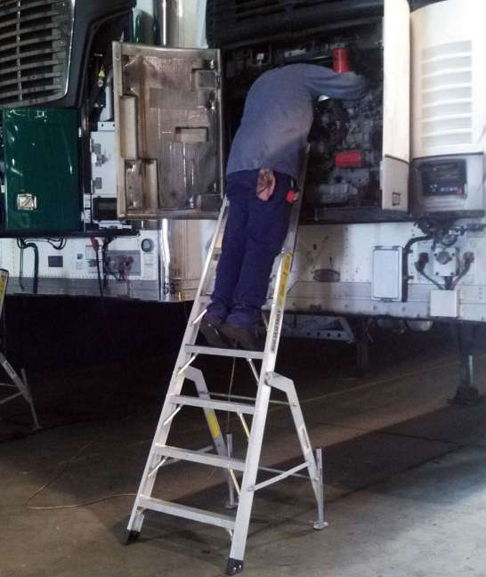 8' MRO Cadet Ladder with tech working on truck AC unit at the shop
