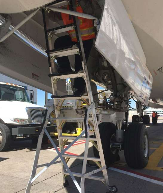 9 Foot Lnc Pylon Ladder With Technician Working In Nose Gear Door Of Boeing 787 On Tarmac
