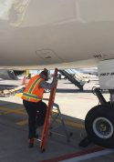 Ee Lite With Technician Getting Down From Access Panel Of Boeing 787